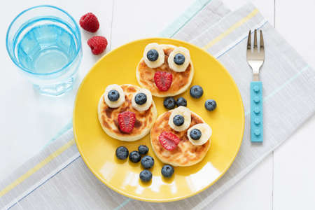 Breakfast for kids. Funny animal face pancakes with fresh berries on yellow plate and glass of pure still water. Top view