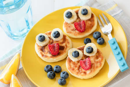 Fun food for kids. Pancakes with funny animal faces on colorful yellow plate. Kids meal. Selective focus