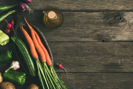 Food background, fresh organic vegetables on old rustic wooden planks. Top view with copy space for text