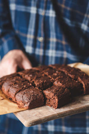 Freshly baked brownies on wooden serving board. Hands holding tray with brownies Фото со стока