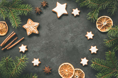 Christmas or New Year 2019 Frame Background. Gingerbread cookies, spices, fir tree and cinnamon on concrete background. Copy space for text Фото со стока