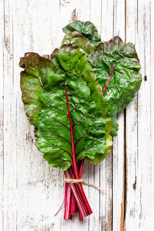 Swiss chard leaf on white wooden background. Top view. Organic green healthy food Фото со стока