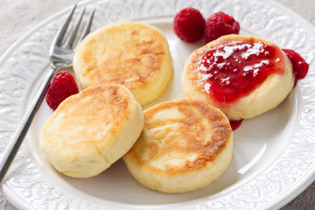 Cottage cheese pancakes or syrniki with raspberry jam on white plate, closeup view. Russian, Ukrainian cuisine. Healthy tasty breakfast