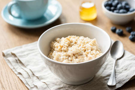 Oatmeal porridge, scottish oats in a bowl on table, kitchen linen. Healthy breakfast, healthy lifestyle concept