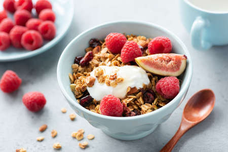 Granola bowl with yogurt, figs and raspberries. Healthy breakfast, healthy snack, concept of healthy lifestyle and eating. Closeup view, selective focus. Blue crockery