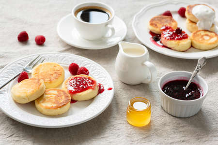 Cottage cheese pancakes with jam, honey and sour cream. Syrniki, sirniki. Russian, Ukrainian cuisine. Healthy tasty breakfast on table covered with linen Фото со стока