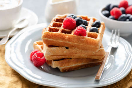 Homemade belgian waffles with berries for breakfast. Closeup view Фото со стока