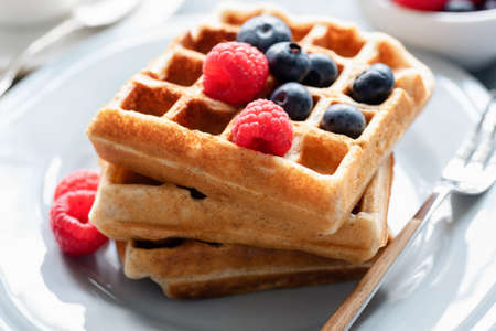 Belgian waffles with fresh berries raspberry blueberry on a plate, closeup view Фото со стока