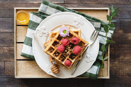 Belgian waffles with honey and raspberries for breakfast. Waffles decorated with flower, berries, granola and honey on wooden serving tray. Top view Фото со стока