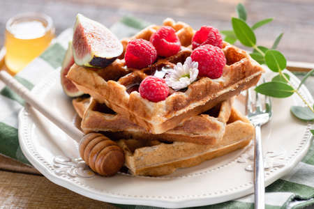 Belgian waffles with raspberries, honey and figs on a plate. Closeup view. Morning breakfast food photography