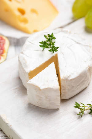 Brie or camembert cheese on white board. Closeup view, selective focus Stock Photo