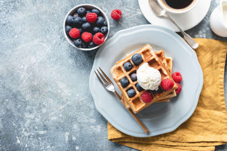 Belgian waffles with ice cream and berries on concrete background. Top view of sweet tasty breakfast. Copy space for your text Stock Photo