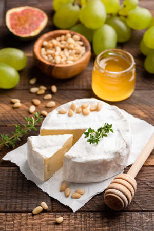 Brie or camembert with pine nuts, figs, honey and green grapes on brown wooden serving board. Closeup view, selective focus Stock Photo