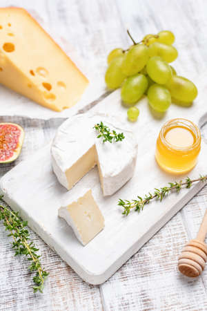 Camembert or brie cheese on white wooden serving board with honey, green grapes, figs and thyme. Top view, selective focus