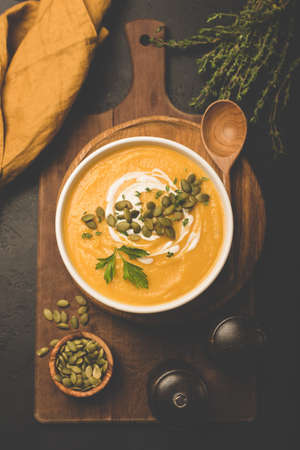 Pumpkin cream soup with pumpkin seeds on wooden serving board. Top view, toned image. Comfort food for Autumn, Fall