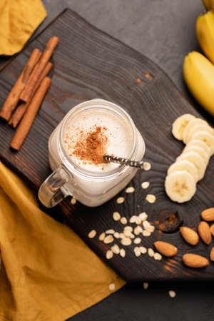Banana milkshake or protein smoothie drink with cinnamon and oats. Top view, selective focus Stock Photo