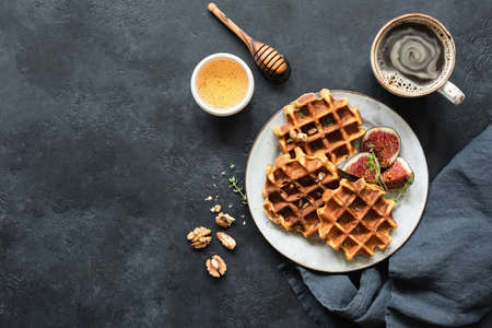 Whole wheat waffles with honey and figs on black concrete background. Top view, copy space for text Stock Photo