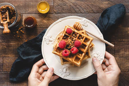 Eating waffles for breakfast. Person holding plate of belgian waffles with raspberries, granola and honey. Tasty breakfast concept, toned image