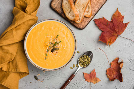 Pumpkin soup puree or cream soup in bowl. Autumn comfort food on concrete background. Warming bowl of soup Stock Photo