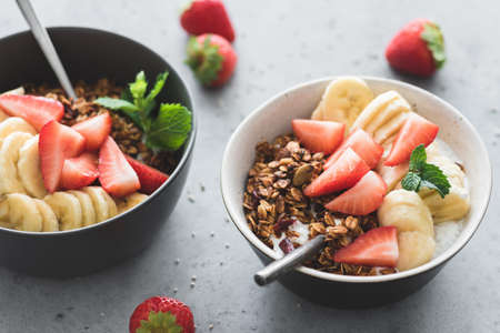 Healthy breakfast bowl with fruits, granola and yogurt on concrete table. Closeup view, toned image