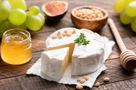 Brie or camembert cheese on brown wooden table served with green grapes, pine nuts, honey and figs. Closeup view. Tasty white cheese Stock Photo