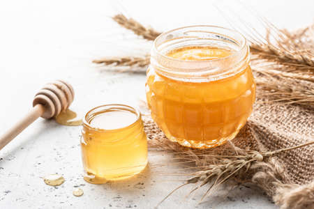 Liquid honey in jar with wooden honey dipper on white concrete background. Healthy lifestyle, healthy eating concept
