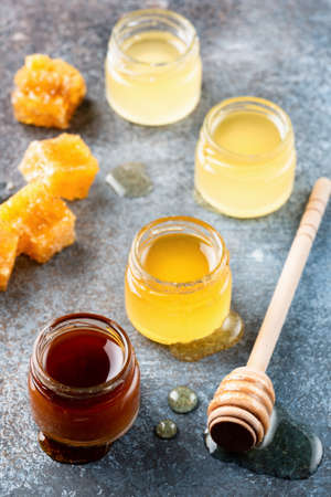 Different types of honey. Acacia, buckwheat honey, wild and raw honey in small jars with wooden honey dipper on dark background