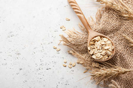 Rolled oats and ears of wheat on concrete background with copy space for text Stock Photo