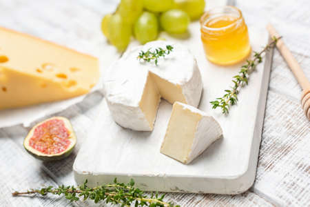 Brie or camembert cheese on white wooden board served with honey, green grapes and figs Stock Photo