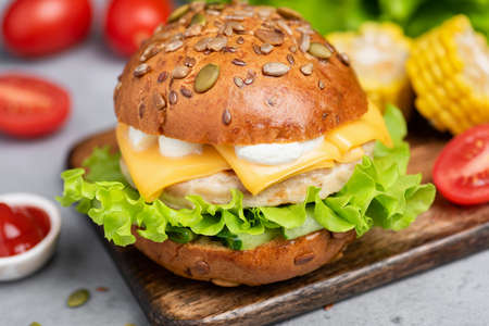 Chicken burger with cheese, lettuce and sauce on wooden serving board. Closeup view. Tasty juicy burger Stock Photo