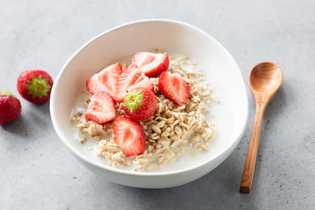 Oats porridge or oatmeal with strawberries in bowl on concrete background. Healthy breakfast food, dieting, weight loss or kids food concept Stock Photo