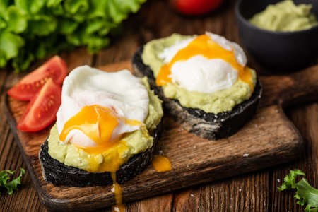 Avocado and poached egg on toasted coal bread on a wooden serving board. Closeup view. Tasty snack, lunch, breakfast food