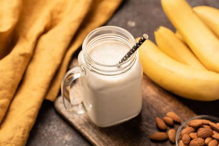 Banana smoothie protein milkshake on wooden serving board. Closeup view, selective focus Stock Photo