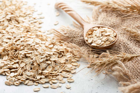 Rolled oats, ears of wheat and wooden spoon. Healthy lifestyle, vegetarian and healthy eating food Stock Photo