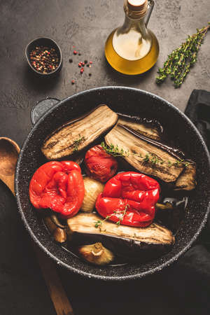 Oven roasted vegetables on pan. Roasted eggplant, red bell pepper, onion, garlic and tomato. Healthy vegetarian food. Top view, toned image Stock Photo