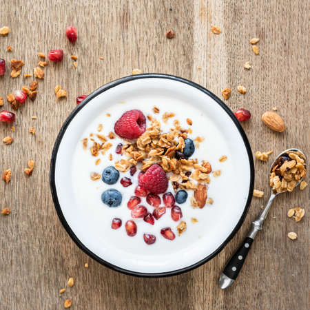 Yogurt with granola, pomegranate seed and berries in a bowl on wooden background. Top view. Healthy breakfast, healthy eating concept