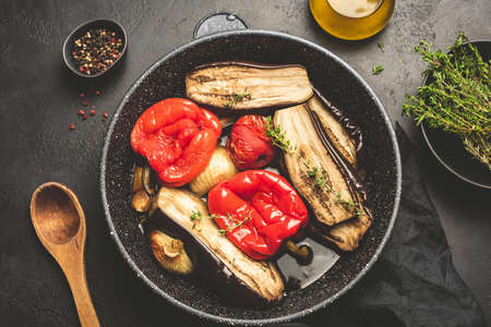 Grilled or roasted vegetables on skillet. Oven roasted eggplant, pepper, tomato, onion, garlic with olive oil and thyme. Top view, toned image