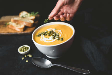 Pumpkin cream soup in bowl on black background. Hand decorating soup with herbs. Food styling concept