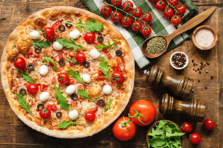 Tasty Italian Pizza With Tomato Mozzarella Cheese Arugula On Wooden Background. Table Top View