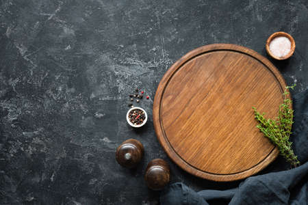 Spices, Herbs, Cutting board for cooking. Round wooden cutting board on black concrete backdrop. Top view with copy space for text. Menu, recipe mock up, banner background Stock Photo
