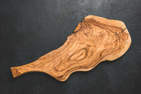 Olive Wood Cutting Board On Black Concrete Background. Top view with copy space for text