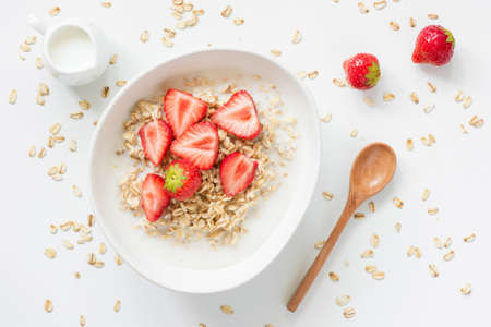 Oatmeal porridge with strawberries and milk in bowl on white background. Top view. Healthy breakfast, vegetarian lifestyle concept Stock Photo