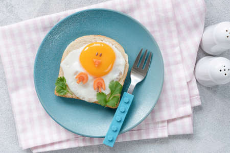 Breakfast for kids. Egg toast with funny cute food art on a blue plate. Top view