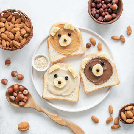 Nut butter toast in shape of cute funny bear for kids served on a white plate. Top view. Creative food art, breakfast for kids, school lunch concept