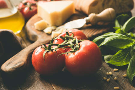 Tomatoes on vine, parmesan cheese, olive oil, basil and ciabatta bread. Italian cuisine food ingredients. Closeup view, toned image Stock Photo