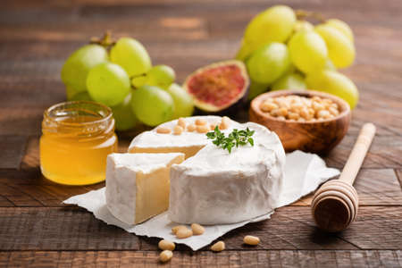 Brie or Camembert cheese with grapes, honey, figs on wooden background. Closeup view Stock Photo