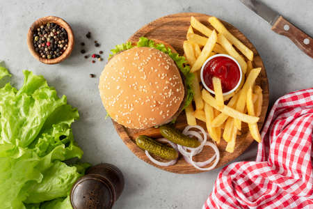Tasty Burger and French Fries On Wooden Serving Board. Table Top View Stock Photo