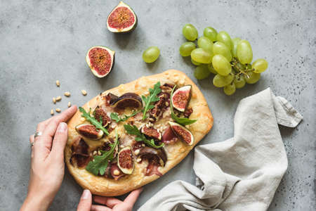 Flatbread pizza with figs, arugula and prosciutto. Hands holding fresh homemade pizza over concrete background, top view