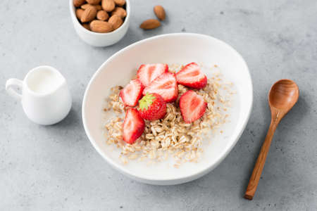 Oatmeal porridge with strawberries and almond milk. Vegetarian or vegan breakfast. Concrete background