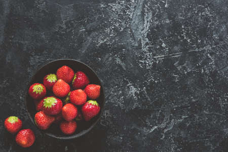 Fresh strawberries in bowl on black concrete background. Top view Stock Photo